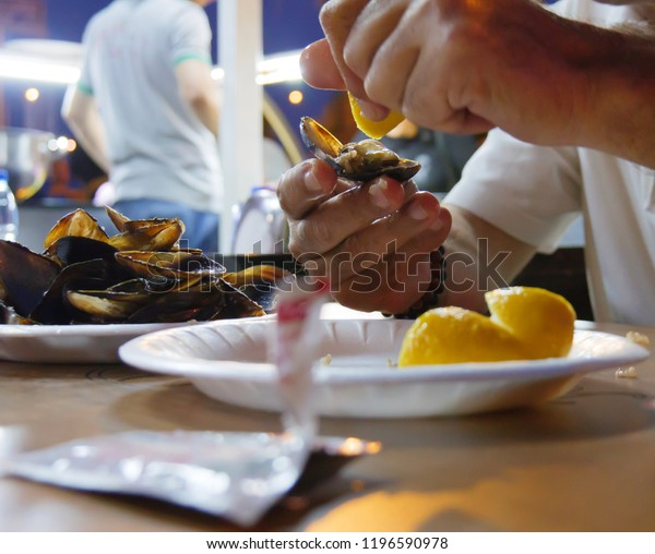 stuffed mussels and man squeeze lemon. midye dolma in Turkish language