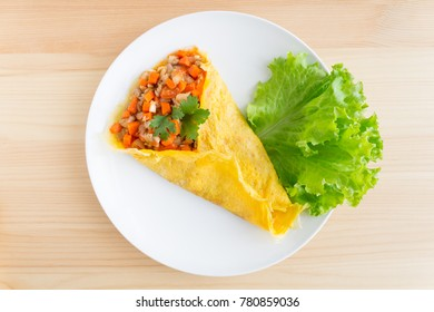 Stuffed omelet with carrot pork onion lettuce coriander in white dish. Stuffed omelet food. Delicious stuffed omelet or fried eggs for breakfast. Stuffed 