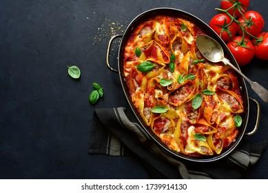 Concannelloni farci de pâtes à la viande hachée cuite à la sauce tomate dans un poêle sur fond d'ardoise sombre, de pierre ou de béton. Vue supérieure avec espace de copie.
