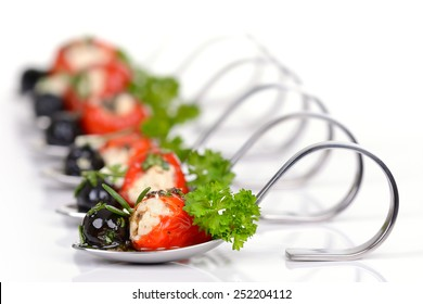 Stuffed peppers, black olives and feta cheese on appetizer spoons