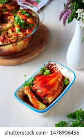 Stuffed peppers with rice, lentils and vegetables cooked with tomato sauce in oven in white ceramic tray
