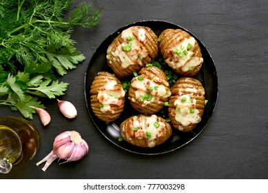 Stuffed potatoes with bacon, green onion and cheese on dark background. Dish for dinner. Top view, flat lay food