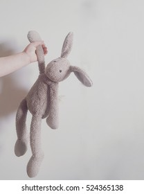 stuffed rabbit holding the ear, hand kid and soft gray background. toys and kids scene