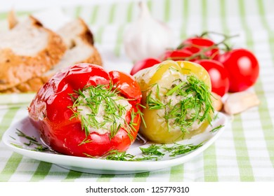 Stuffed red and green peppers on a white plate.