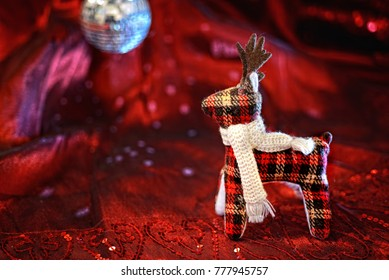 stuffed reindeer over red background with disco ball in background