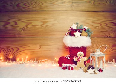 Stuffed Santa Claus boot with sweets and gingerbread man in the snow.Cute rustic background
