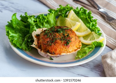 Stuffed seasoned clams garnished with romaine lettuce and lemon wedges on a marble kitchen table