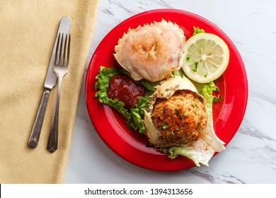 Stuffed seasoned crab shells garnished with romaine lettuce and sliced lemon with cocktail sauce