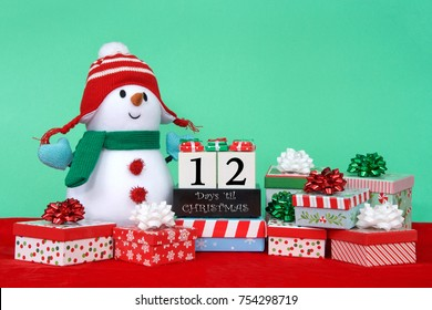 Stuffed Snowman with green scarf, blue mittens, red and white hat sitting on red velvet surrounded by bright colorful presents, blocks count down to christmas. 12 days