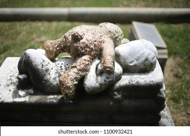 Stuffed Teddy Bear Lying on Top of a Child's Grave Baby Marble Statue Grave Memorial Marker