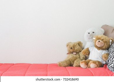Stuffed up teddy bears on bed of a child. White wall in the background. Negative space. Concept.