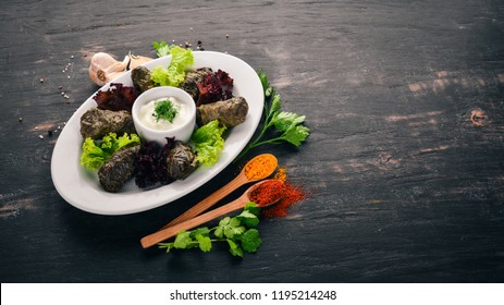 Stuffed vine leaves, dolma, sarma, dolmadakia, dolmades are a white plate. On the old wooden background. Free space for text. Top view.