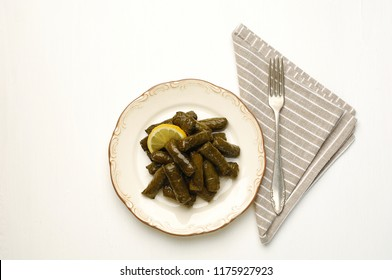 stuffed vine leaves on a plate, a napkin and a fork on the side, isolated on white background, sarma, dolma, dolmades, dolmadaki, dolmas