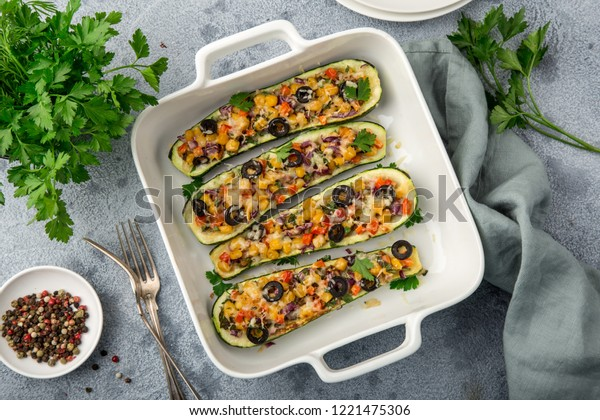 Stuffed zucchini boats with vegetables ( tomato, pepper, corn, red onion and olives) and cheese in white baking dish,  top view