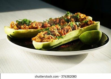 Stuffed zucchini on a black plate decorated with parsley.