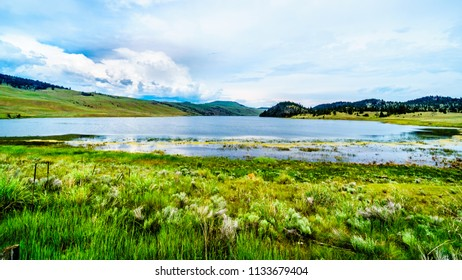 Stump Lake surrounded by the Rolling Hills and wide open Grass Lands of the Nicola Valley along Highway 5A, between Merritt and Kamloops, British Columbia, Canada, under partly cloudy sky