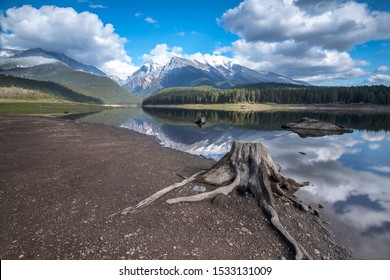 A stump sits in the foreground at Mission reservoir and high peak snow covered mountains near St. Ignatius, Montana
