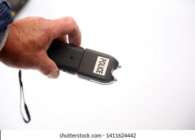 Stun Gun. Police Stun Gun. A mans hand activates a Stun Gun demonstrating the Electric Arc generated. Self Defense weapon.
