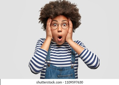Stunned African American female stares at camera and keeps mouth opened, scratches head and looks surprisingly, realizes bad news, stands against white background. People, reaction, ethnicity
