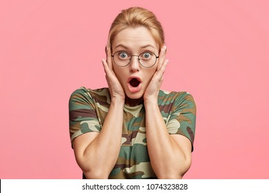 Stunned blonde female model in eyewear, being astonished with something, keeps mouth opened, dressed in camouflage t shirt, isolated over pink background. Beautiful woman says: It`s incredible
