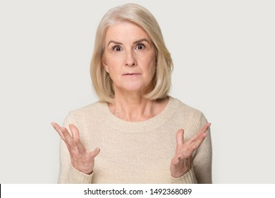 Stunned Caucasian senior woman isolated on grey studio background feel surprised by deal or promotion, amazed aged female look at camera shocked by unexpected unbelievable sale offer