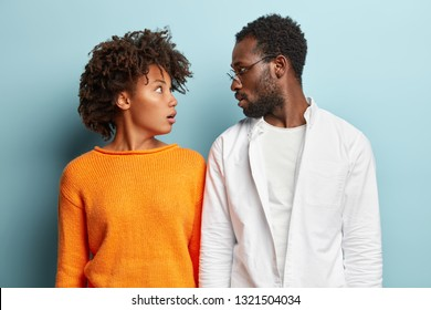 Stunned dark skinned female and male partners look surprisingly at each other, forget to accomplish important task, dressed in casual outfit, isolated over blue background. Puzzled ethnic couple