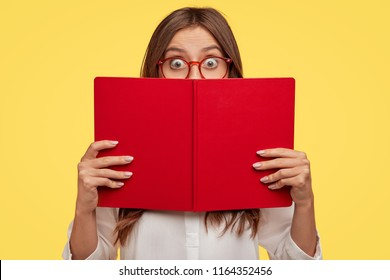 Stunned emotive student nerd hides face behind opened red book, wears glasses, does some tasks and prepares for classes in university, stands against yellow background. Girl enjoys reading literature