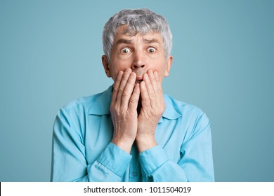 Stunned frightened elderly male model covers mouth with hands, being surprised and scared to hear shocking news, can`t believe in disaster, isolated over blue background. People and reaction