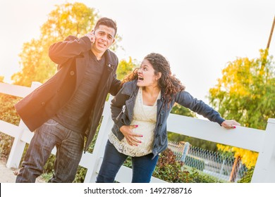 Stunned Hispanic Pregnant Young Couple In Pain Walking Outdoors.