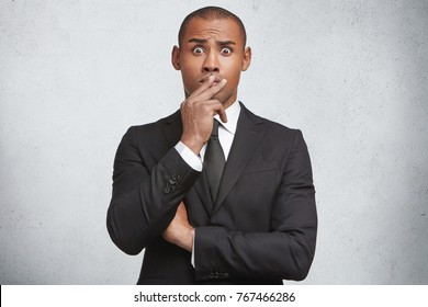 Stunned shocked young male boss or office director covers mouth with hand, surprised to hear about falling sales, tries to solve problem, wears formal clothes, isolated over white background.