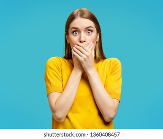 Stunned young girl closes her mouth with her hands, looks at camera. Photo of attractive girl in yellow sweater on blue background