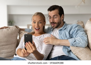 Stunned young man and woman user look at smartphone screen shocked by unexpected news online. Amazed Caucasian couple clients or buyers surprised by good sale offer or promotion deal on cellphone.
