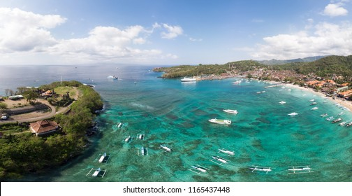 Stunning aerial panorama of Padang Bai beach, harbor and town in Northeast Bali in the famous Indonesia island on a sunny day.