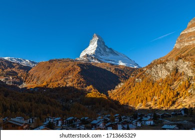 Stunning aerial panorama view of Zermatt town with the famous Matterhorn peak of Swiss Alps in background and golden forest on sunny autumn day with blue sky, Valais, Switzerland