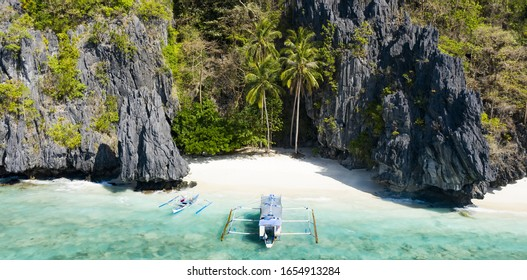 Stunning aerial view the Entalula Beach, a white sand beach surrounded by rocky formations and bathed by a crystal clear sea. Entalula island, Bacuit Bay, El Nido, Palawan, Philippines.