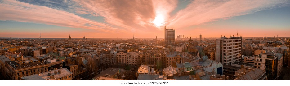 Stunning aerial view of Riga, Latvia during purple orange sunset. View of the old town, suspension bridge and river Daugava.