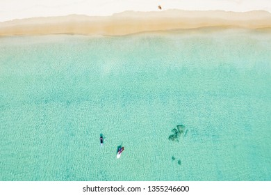 Stunning aerial view of two unidentified people doing stand up paddle board and windsurf on a clear and turquoise sea while a woman sunbathing on a white beach. Surin beach, Thailand.
