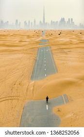 Stunning aerial view of an unidentified person walking on a deserted road covered by sand dunes in Dubai desert. Dubai skyline surrounded by fog in the background. Dubai, United Arab Emirates.