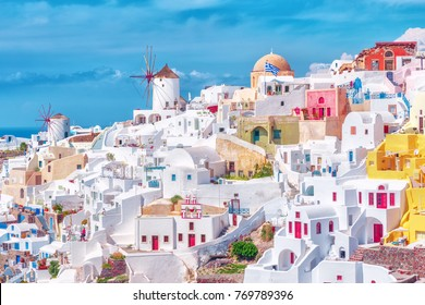 Stunning, amazing and beautiful classic white and caramel  color Greek architecture with unbelievable wind mills on Santorini volcano Cyclades Caldera island in warm waters of Aegean sea in Greece.