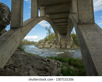 a stunning arched concrete bridge somewhere in foothills