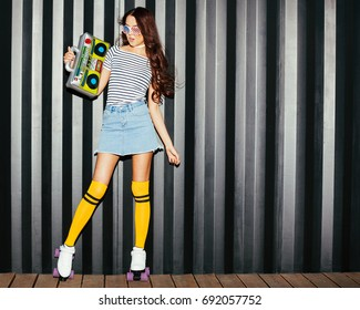 Stunning asian girl look at camera in a denim skirt, T-shirt and American sunglasses enjoys music with a vintage ghettoblaster and roller skates. Flash shooting at night on the street. Outdoor.