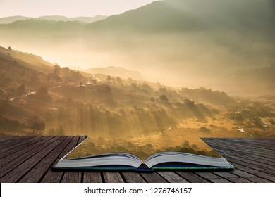 Stunning Autumn Fall landscape sunrise in the Lake District with sun beams streaming through the mist into The Langdales valley coming out of pages of open story book