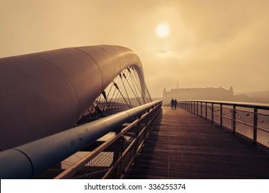 Stunning autumn foggy morning. Couple walking through Bernatka bridge over Vistula river in Krakow, Poland.