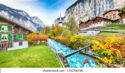 Stunning autumn view of Lauterbrunnen village with awesome waterfall  Staubbach  and Swiss Alps in the background.  Location: Lauterbrunnen village, Berner Oberland, Switzerland, Europe.