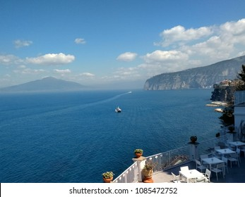 Stunning balcony view over white railings from cliff top at Sorrento Bay Of Naples Italy looking over blue sea towards volcanic Mount Vesuvius and rock face with ship in water on holiday in Summer sun
