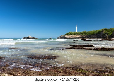 Stunning beach in Biarritz with clear water and the lighthouse in the background. Basque coast of France.