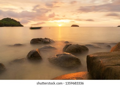Stunning beautiful landscape at rocky beach during sunset with calm dreamy sea captured using long exposure camera setting.