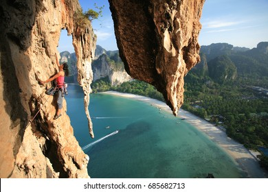 Stunning beautiful professional female rock climber, climbing mountain multi pitch in Thailand cliff, at Railay beach cliffs and coconut trees on the background in Krabi Province