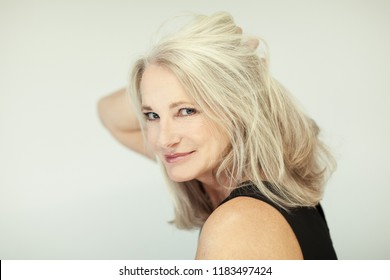 stunning beautiful and self confident best aged woman with grey hair smiling into camera, portrait with white background