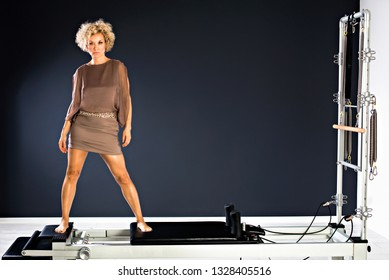 stunning beautiful and self confident best aged woman standing on tower reformer in fitness studio